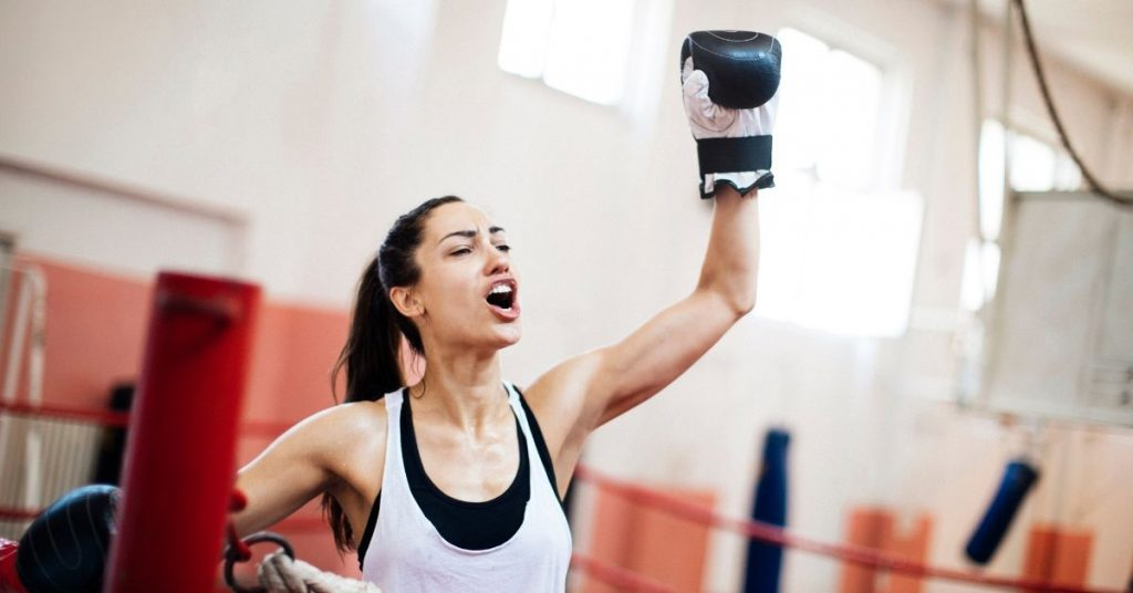 a woman with a ponytail and a vest top with one boxing glove in the air, shouting in victory