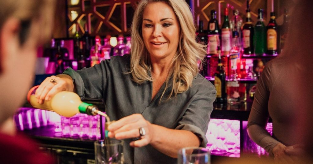 female bartender pouring the measurements for a cocktail