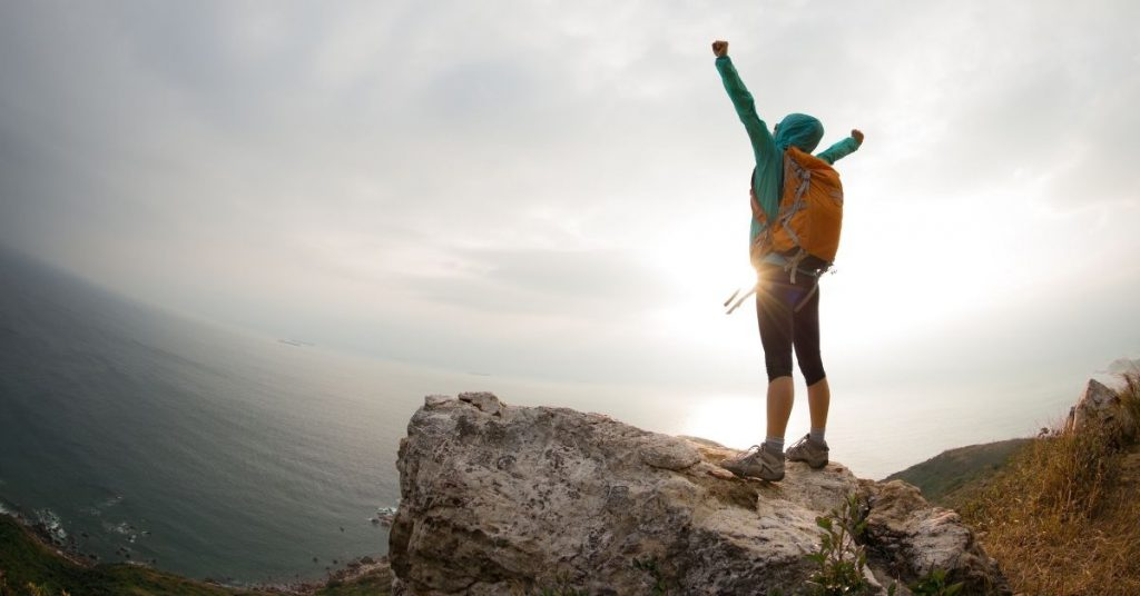 person on a cliff overlooking the sea with a backpack on, their hands raised to the sky with a sense of accomplishment.